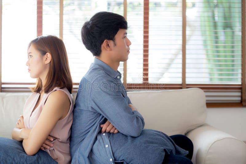 Relación de los pares asiáticos jovenes que tienen problema en el sofá en la sala de estar en casa fotografía de archivo