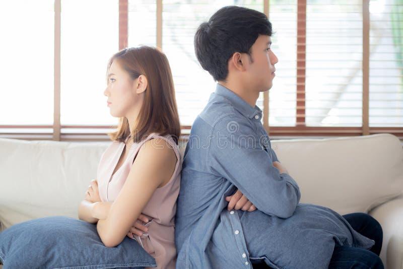 Relación de los pares asiáticos jovenes que tienen problema en el sofá en la sala de estar en casa, familia que tiene discusión d fotografía de archivo libre de regalías