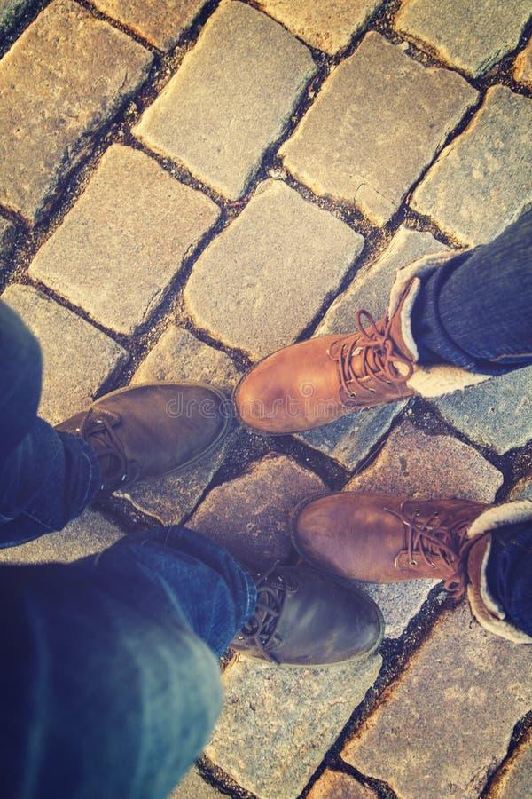 Relación en un par de los amantes, dos de lado a lado pies en zapatos en las losas foto de archivo