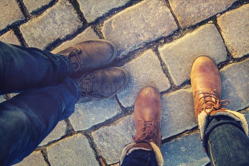 Relacionamento em um par de amantes, bilateral perto pés nas sapatas nos pavimentos fotografia de stock royalty free