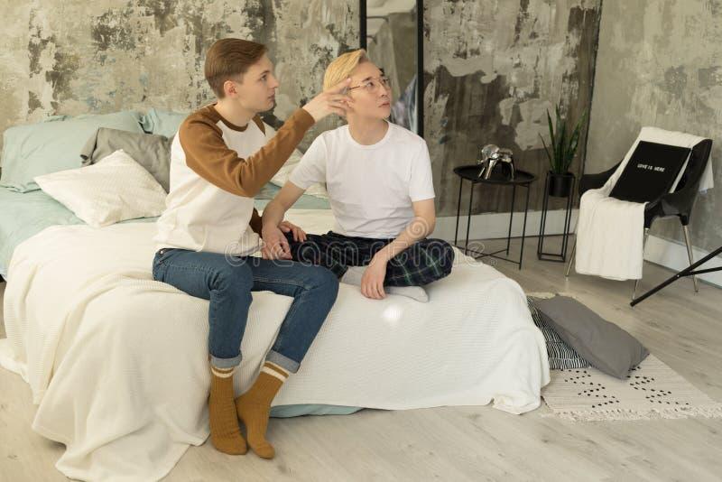 Relacionamentos adultos internacionais Dois sócios masculinos alegres na roupa ocasional que descansa junto em uma cama foto de stock royalty free