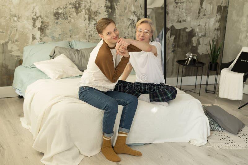 Relacionamentos adultos internacionais Dois s?cios masculinos alegres na roupa ocasional que descansa junto em uma cama fotos de stock royalty free