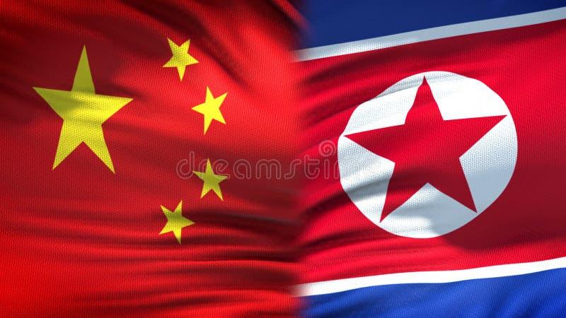 Relaciones del fondo de las banderas de China y de Corea del Norte, diplomáticas y económicas fotografía de archivo