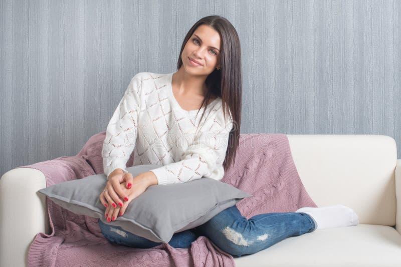 Relajándose en casa, comodidad sonrisa linda de la mujer joven, relajándose en el sofá blanco, sofá en casa foto de archivo
