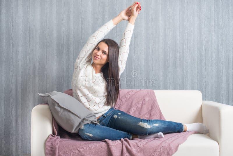 Relajándose en el sofá, sofá en casa, comodidad sonrisa linda de la mujer joven, fotografía de archivo