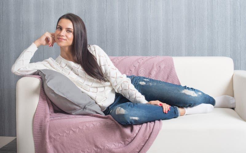 Relajándose en el sofá, sofá en casa, comodidad sonrisa linda de la mujer joven, imagen de archivo