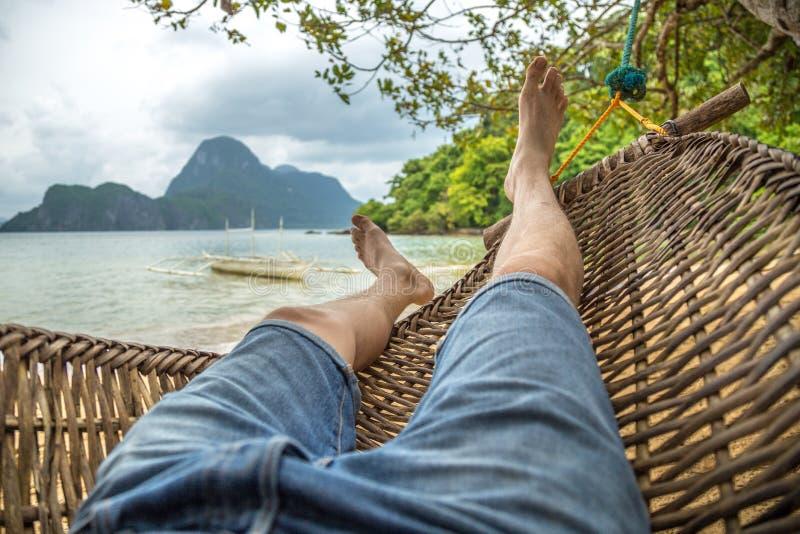 Relajándose en la hamaca, los pies desnudos se cierran para arriba, día de verano nublado en la montaña y fondo del mar imagenes de archivo