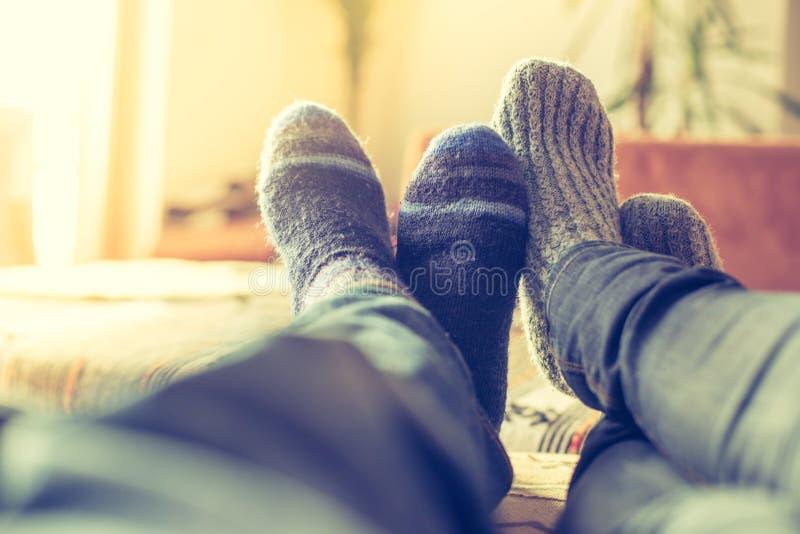 Relajación acogedora en el invierno en casa: El par con los calcetines de lana está mintiendo en el sofá imagen de archivo libre de regalías