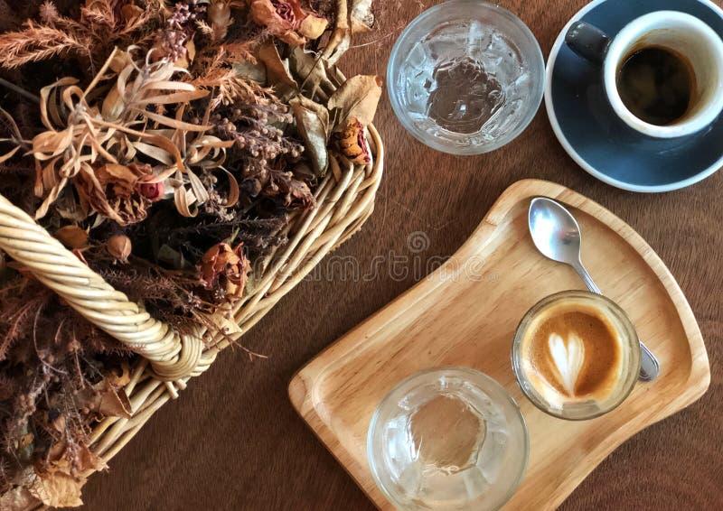 Relajación con el tiro del café express y el arte de flautín del latte y flores secadas en una cesta en la tabla de madera fotografía de archivo libre de regalías