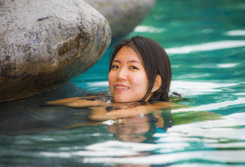 Relajación coreana asiática atractiva y hermosa joven de la mujer feliz en la natación tropical del centro turístico de lujo de l foto de archivo libre de regalías