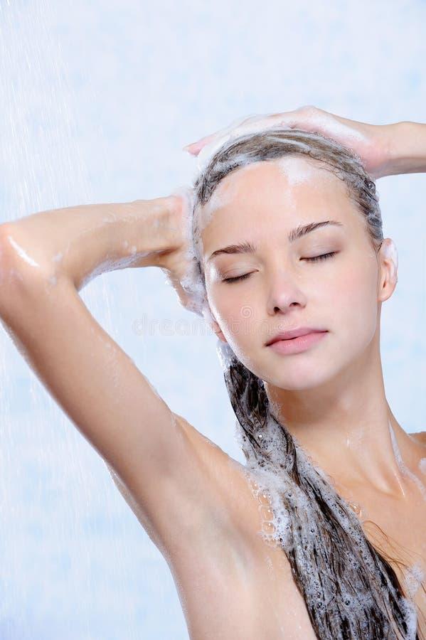 Relajación de la mujer joven que toma la ducha imagenes de archivo