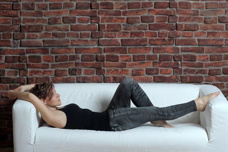 Relajación de mentira de la mujer delgada joven en el sofá imagenes de archivo