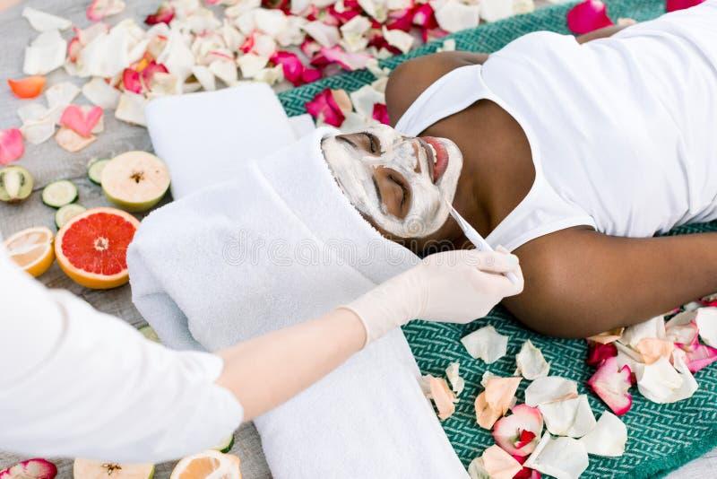 Relajación de reclinación de la muchacha africana hermosa en balneario con los ojos cerrados mientras que el cosmetologist aplica imagen de archivo