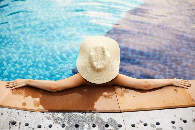 Relajación en complejo playero Mujer hermosa en sombrero grande que disfruta de verano en piscina Concepto de lujo del viaje y de fotografía de archivo libre de regalías