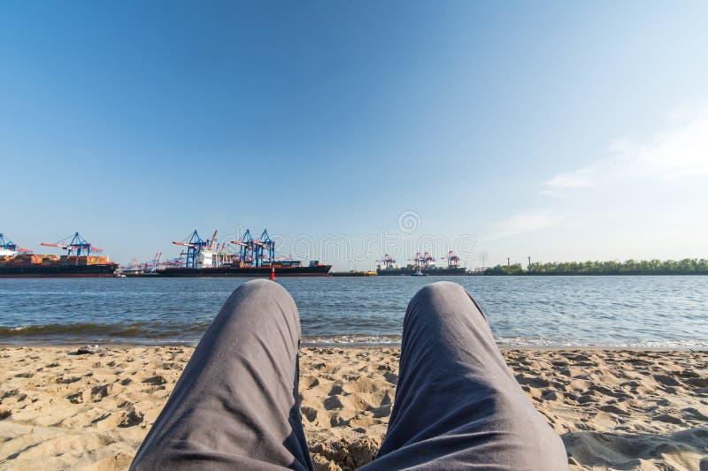 Relajación en la playa de Elba en Hamburgo con el puerto y las naves en el fondo imagen de archivo
