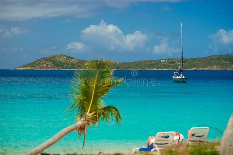 Relajación en silla en la playa con la palma y el yate en fondo imagen de archivo