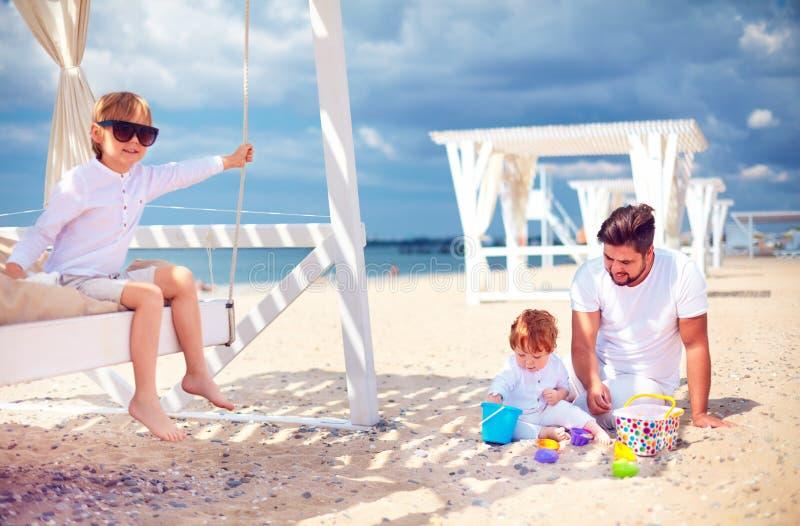 Relajación feliz de la familia, jugando en la playa en las vacaciones de verano foto de archivo