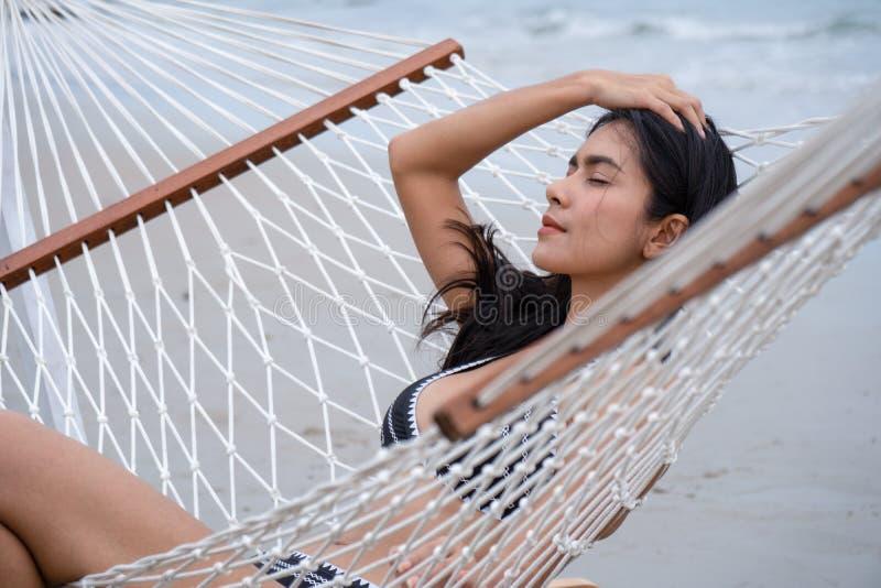 Relajación femenina en hamaca en la playa imágenes de archivo libres de regalías