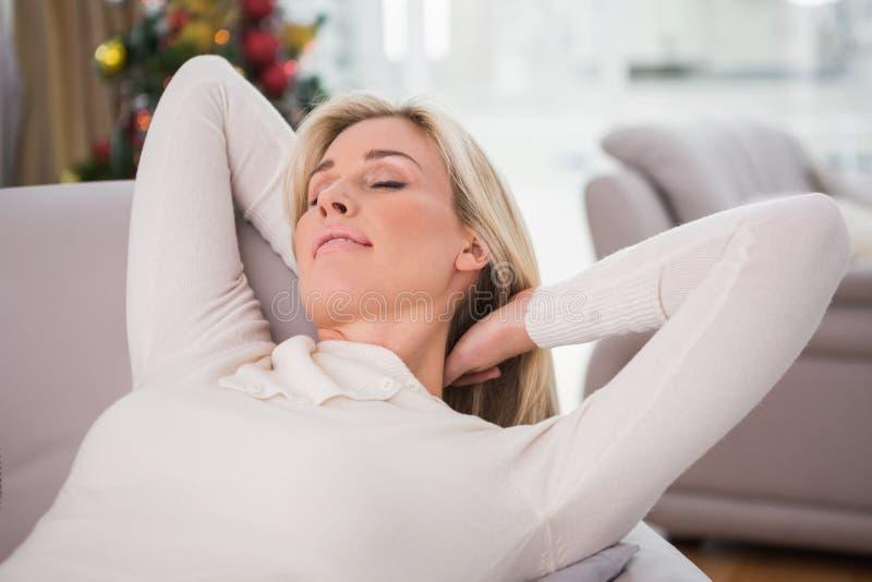 Relajación rubia en el sofá en la Navidad imagen de archivo libre de regalías