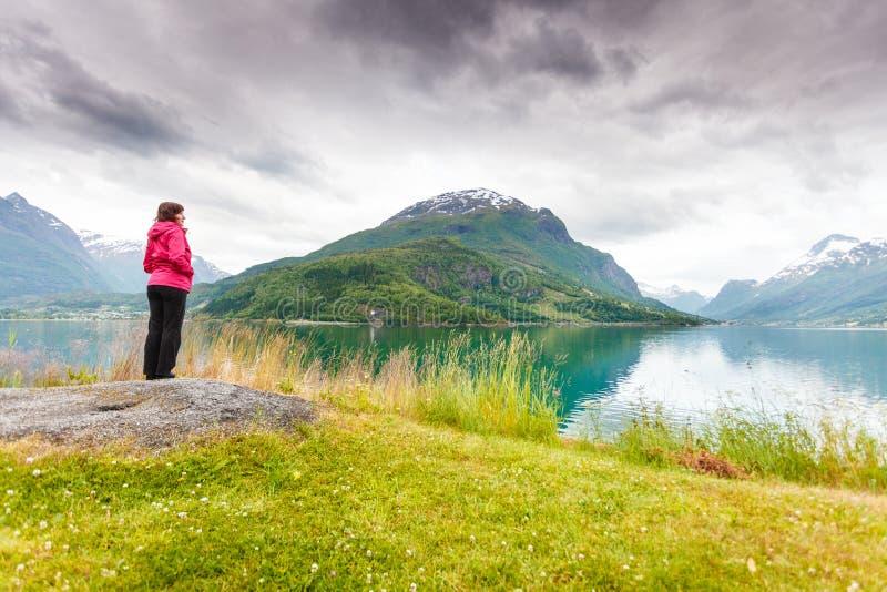 Relajación turística de la mujer en la orilla de mar del fiordo, Noruega imagen de archivo