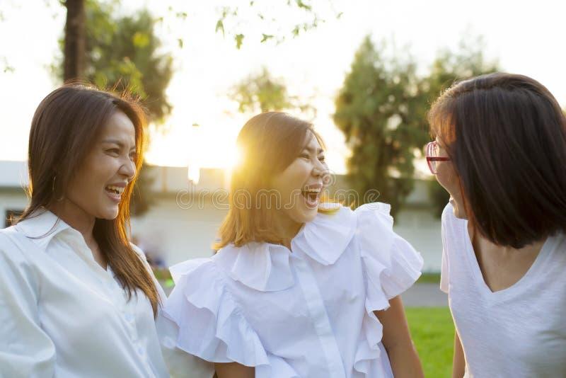 Relajaci?n asi?tica de la mujer tres al aire libre con la cara de la felicidad fotografía de archivo libre de regalías
