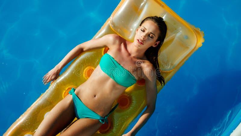 Relajaci?n y sol de la mujer que broncean por la piscina fotos de archivo