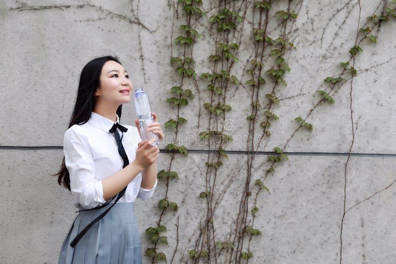 Relaje al estudiante bonito chino asiático del desgaste de las muchachas que el traje en escuela goza del agua de la bebida del t foto de archivo libre de regalías