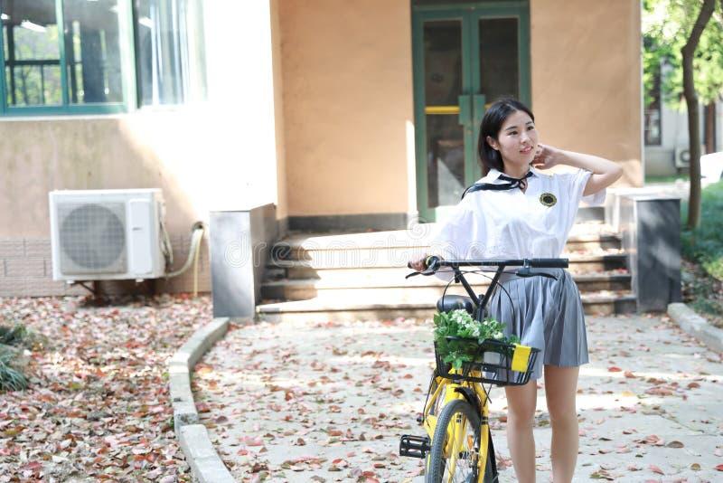 Relaje al estudiante bonito chino asiático del desgaste de las muchachas que el traje en escuela goza de la bici del paseo del ti fotografía de archivo libre de regalías