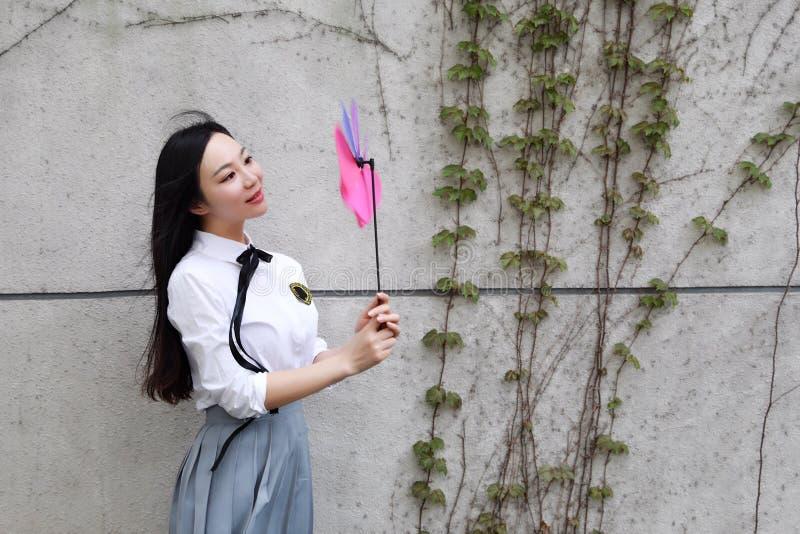 Relaje al estudiante bonito chino asiático del desgaste de las muchachas que el traje en escuela goza del molino de viento del ju foto de archivo