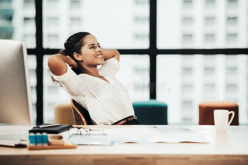 Relaje el tiempo Empresaria acertada que se relaja y que descansa después de sentarse y del funcionamiento duro imagen de archivo libre de regalías