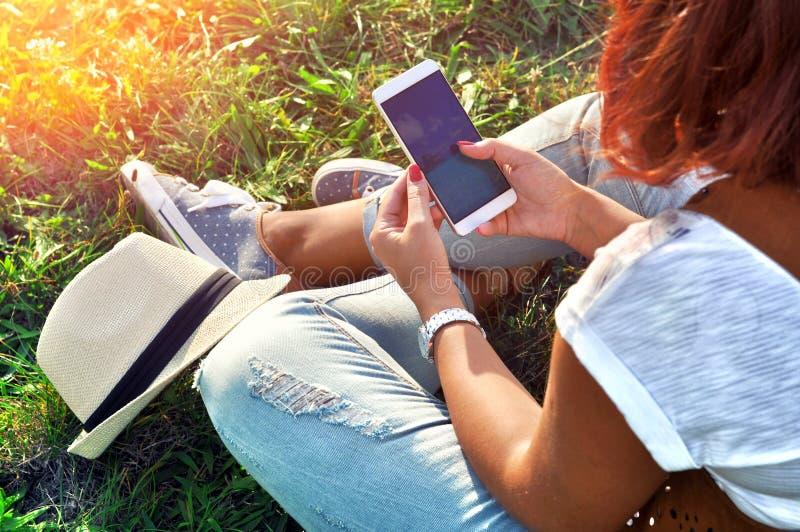 Relaks z wiszącą ozdobą Przerwa czas Młoda kobieta używa telefon komórkowego i obsiadanie na trawie fotografia stock