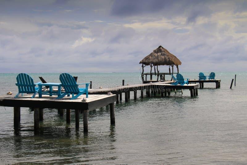 Relaksować Karaibskiego widok od jaskrawych błękitnych drewnianych loungers fotografia royalty free