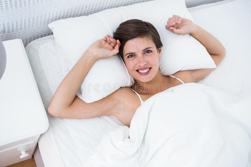 Relaksująca kobieta ono uśmiecha się przy kamerą w jej łóżku obraz royalty free