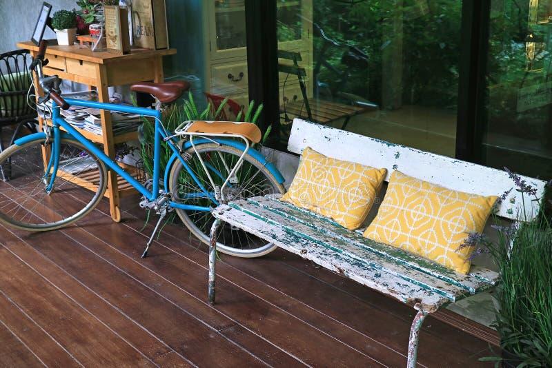 Relaksująca przestrzeń przy tarasem z wygodną ławką i bicyklem obraz stock