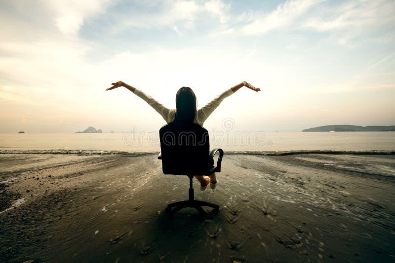 Relaksujący biznesowej kobiety obsiadanie na plaży fotografia stock