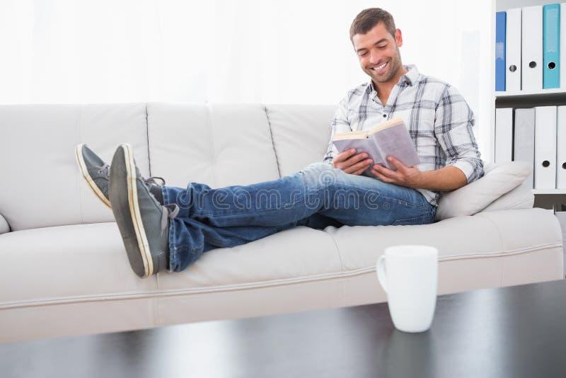 Relaksujący mężczyzna na kanapie z książką zdjęcia royalty free