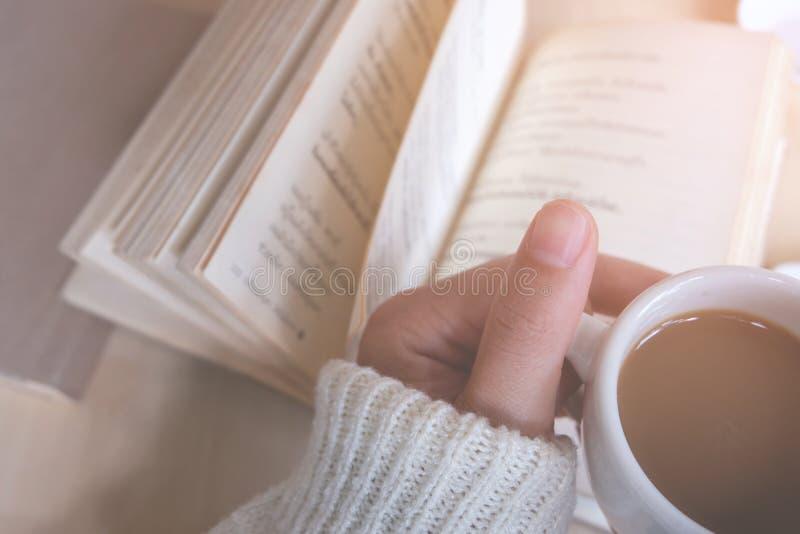 Relaksujący momenty, filiżanka kawy, książka na drewnianym stole w natury tle, kolor rocznika brzmienie i miękka ostrość, fotografia stock