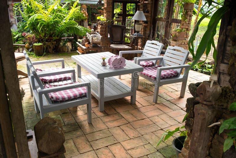 Relaksujący w ogrodowym projekta terenie, biały drewno stół ustawia w obraz stock
