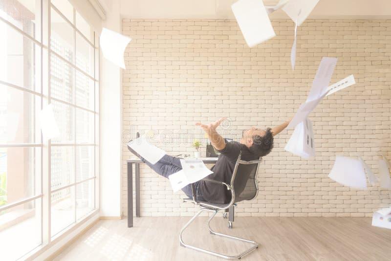 Relaksuje działanie Azjatycki biznesmen podrzuca wiązkę papiery świętuje końcówkę jego sukcesu raport i praca Relaksuje i szczęśl obrazy stock