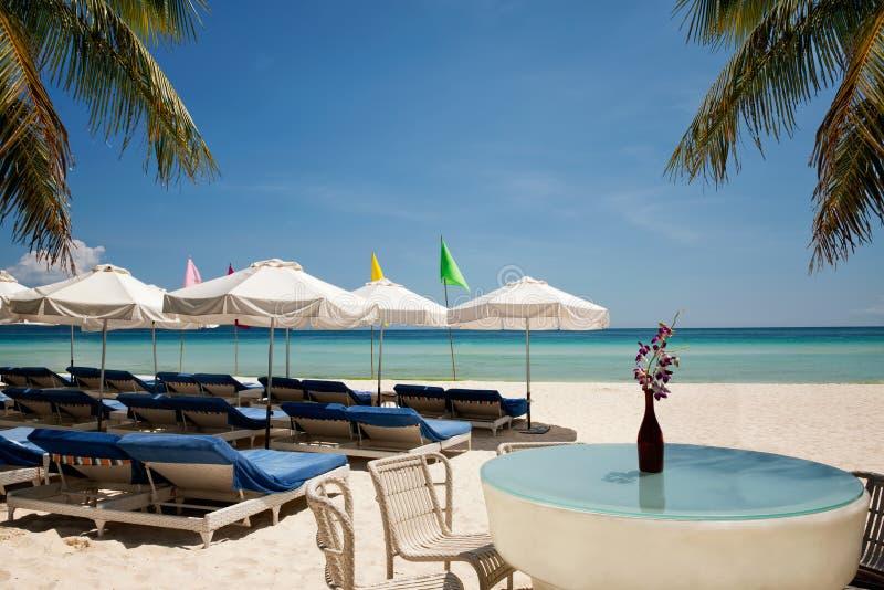 Relaksuje teren na plaży z parasolami od światła słonecznego i palm zdjęcie stock