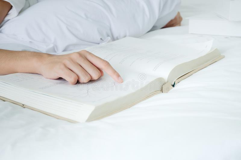 Relaksuje w sypialni, czyta książkę, fotografia royalty free