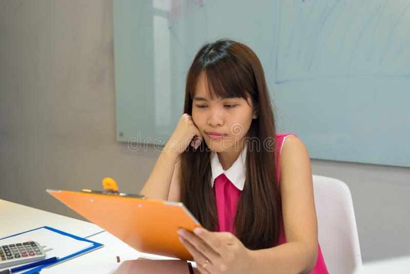 Relatório asiático da leitura do empregado com uma cara bonito foto de stock royalty free