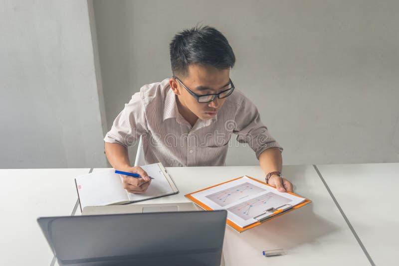 Relatório asiático da leitura do homem e para tomar a nota fotografia de stock royalty free