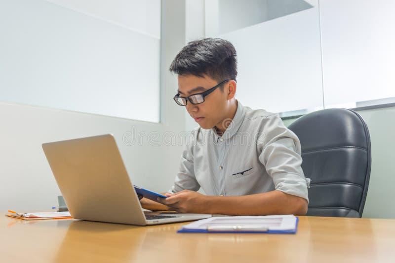 Relatório asiático novo da leitura do homem de negócios no escritório fotos de stock