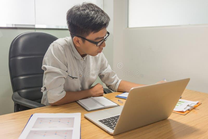 Relatório asiático sério da leitura do homem de negócios no escritório fotos de stock royalty free