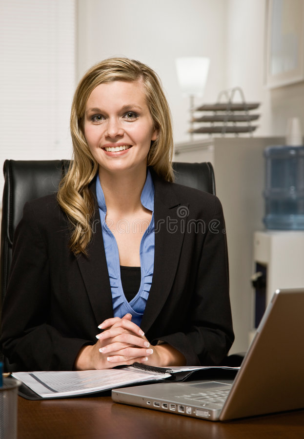 Relatório confiável da leitura da mulher de negócios na mesa fotografia de stock