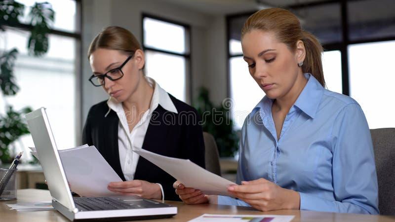 Relatório da leitura do chefe do estagiário, descontentado com baixas taxas, pressão no trabalho foto de stock royalty free