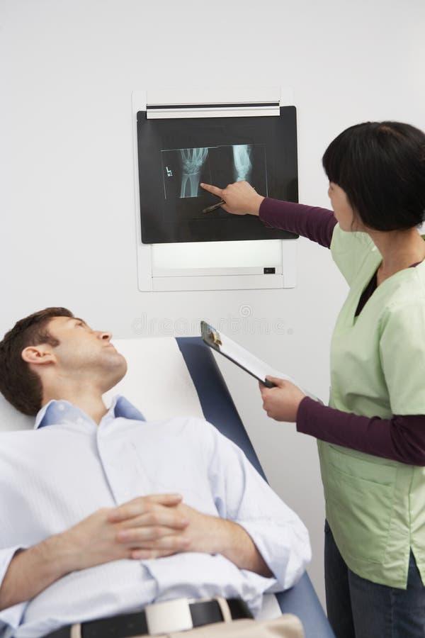 Relatório do raio X do doutor Explaining The ao paciente masculino imagens de stock royalty free