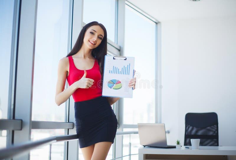 Relatório fêmea de sorriso da carta do lucro da exibição do vendedor imagens de stock royalty free
