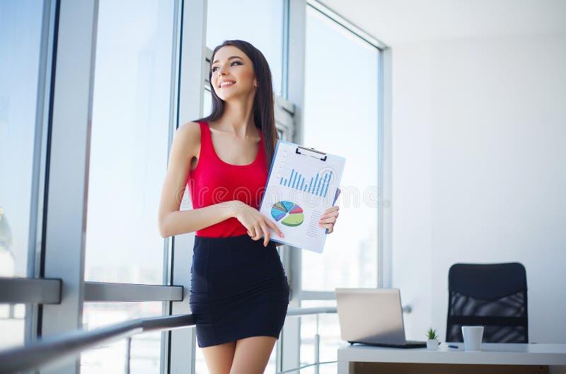 Relatório fêmea de sorriso da carta do lucro da exibição do vendedor imagem de stock